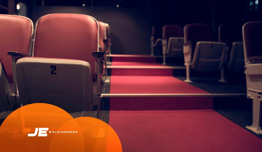 pessoas com deficiência - A imagem possui cadeiras de cinema com um corredor no meio com escadas. As cores predominantes nessa imagem é a bordo.